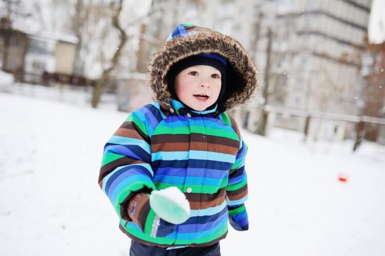 baby boy in striped overalls colored in snow