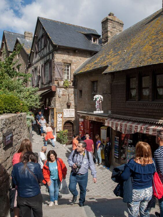 A crowd of tourists on Grand Rue, the main street in Mont Saint Michele. Normandy, France