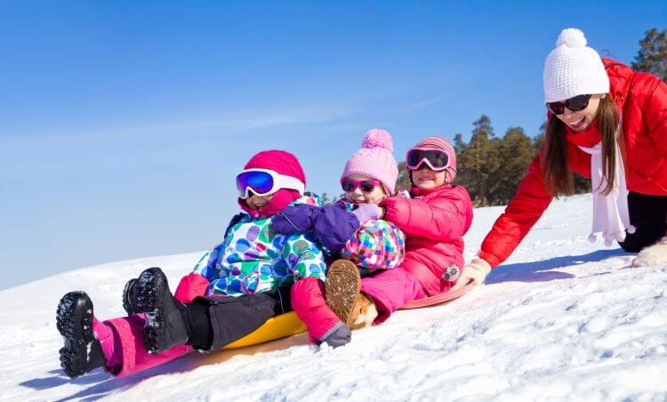 Kids sitting on a sleigh with full winter gear getting ready to slide down a snow hill with mom pushing in the back.