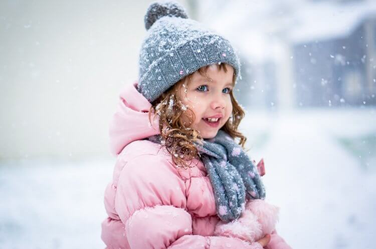 Cute baby girl in pink jacket and grey hat enjoying first snow b