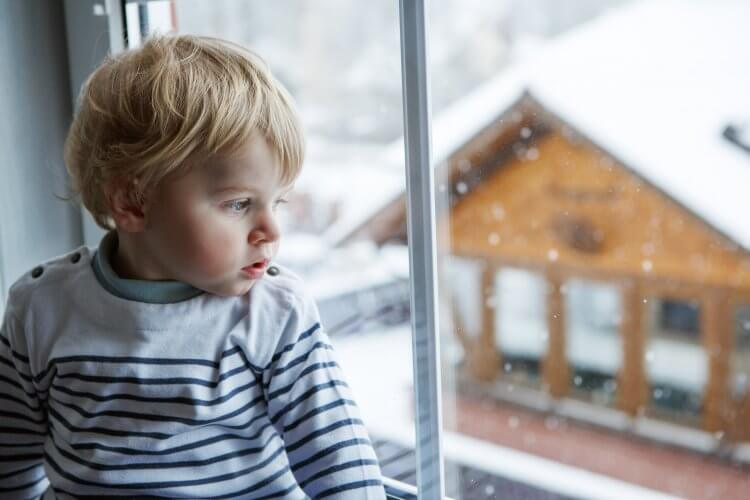 Little toddler boy looking out of the window on winter day with snow landscape