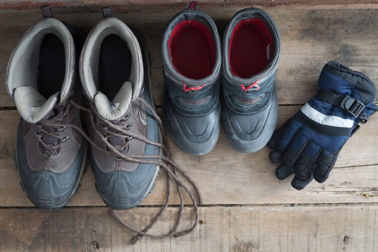 Overhead view of a pair of adult and kids snow boots standing ready on a rustic wooden floor alongside a pair if childs warm winter gloves to protect against the freezing cold weather, view from above
