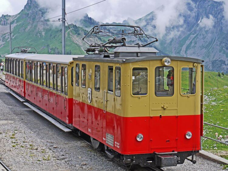 Yellow and red swiss train sitting on the rails alongside the lush green grass and snow capped mountains.