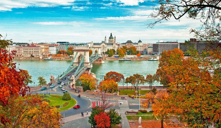 Image of Budapest, Hungary in the Fall with beautiful fall foliage in the trees overlooking the bridge. Check out why Budapest with Kids is the perfect family vacation.