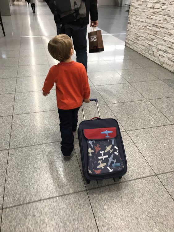 Little boy pulling his suitcase through the airport in Budapest, Hungary.