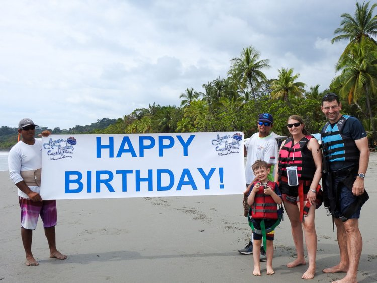 Parasailing with Aguas Azules. Family standing in front of a Happy Birthday sign.
