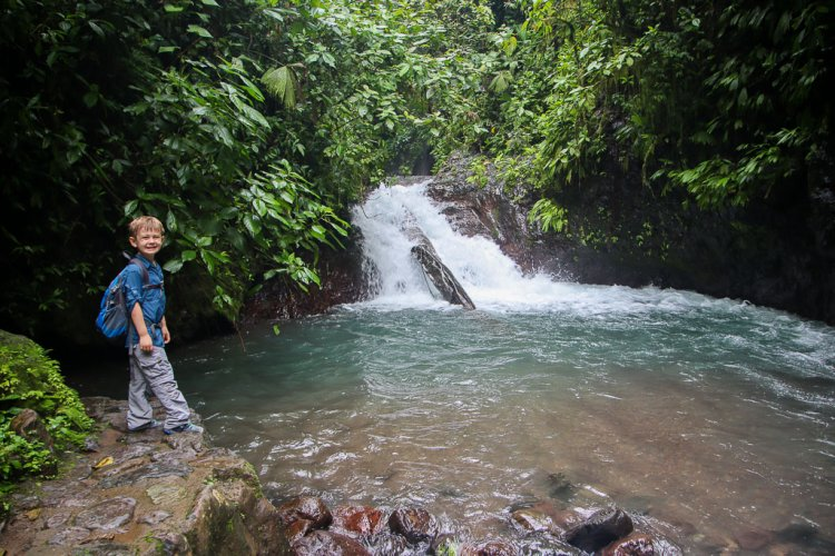 Waterfalls with boy standing on a rock in Rainmaker Costa Rica.