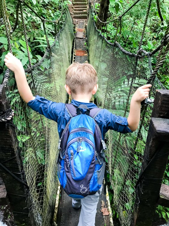 Boy crossing the bridges at Rainmaker Park Costa Rica.