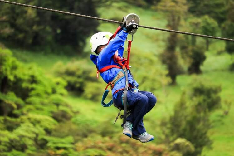 Five year old boy in a blue coat riding on the zip line