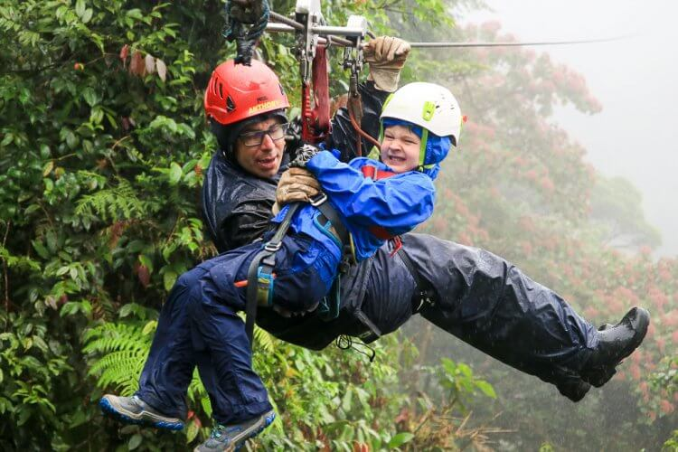 Five year old boy and guide attached to a zipline riding into the platform.