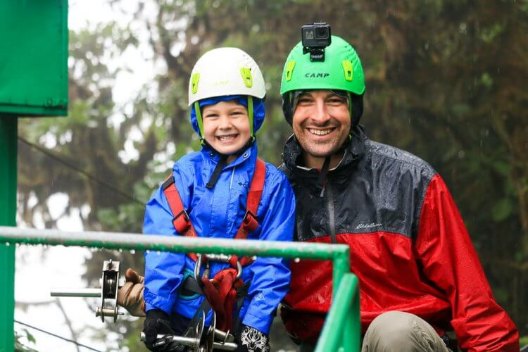 Father and Son, both wearing raincoats and helmets smiling at the camera.