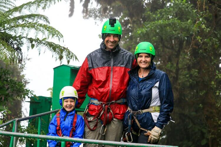 Father, Mother and their five year old son standing on a platform wearing rain jackets, helmets and harnesses smiling at the camera.