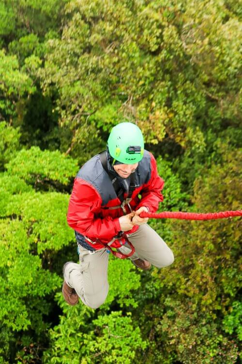 Adult male wearing a red rainjacket, jumping backwards and is currently midair.