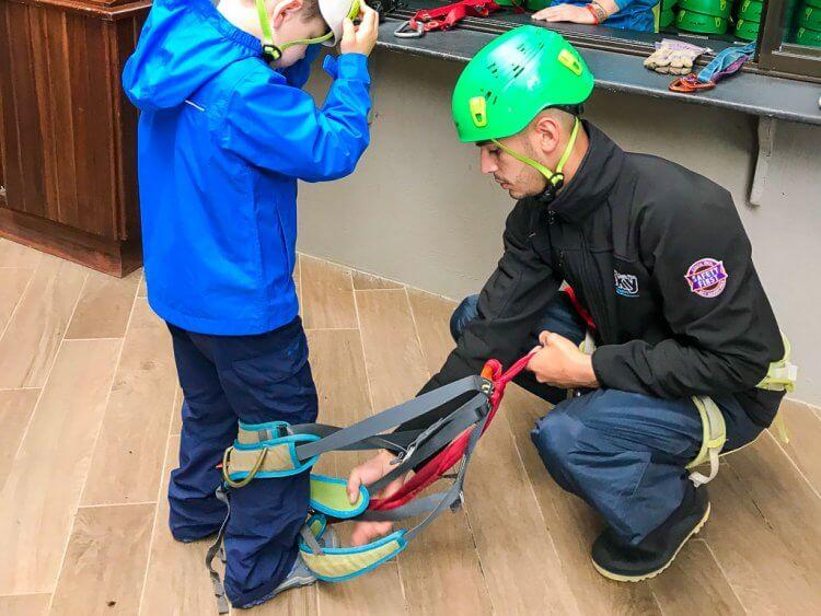 Man helping a little boy inside his harness.