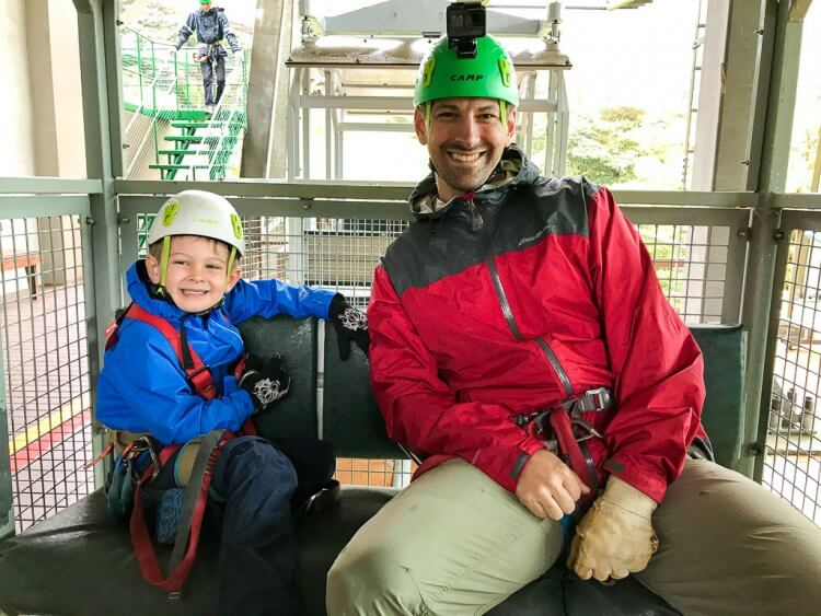 A father in a red jacket and his son in a blue jacket sitting inside a cable car.