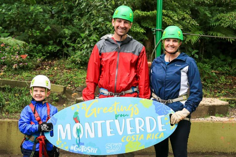 A boy with his mother and father holding a Sky Adventures Monteverde sign.