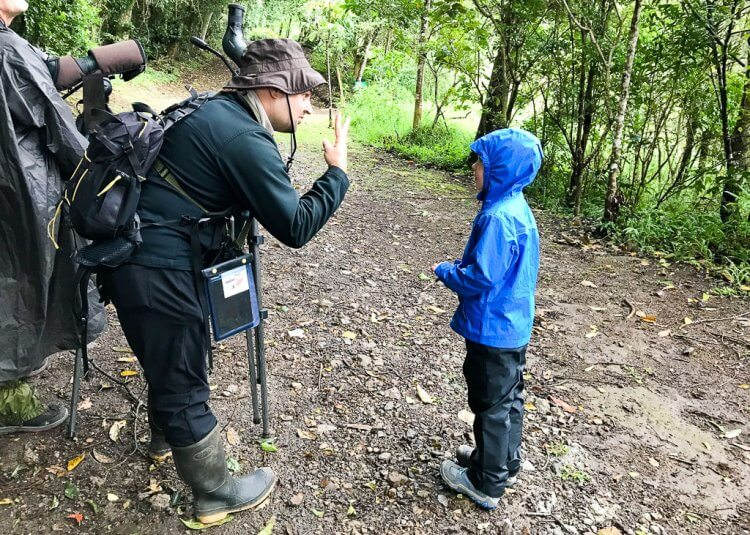 Our Guide, Christian standing with his zoom lens on a tripod, standing next to a little boy with a blue rain jacket.