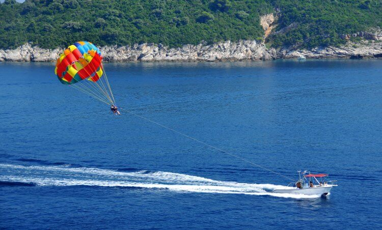 Parasailing behind a boat in the ocean.
