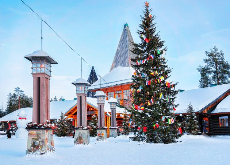 View of a building with a tall spire, large Christmas tree decorated for the season and white snow blanketing the ground.
