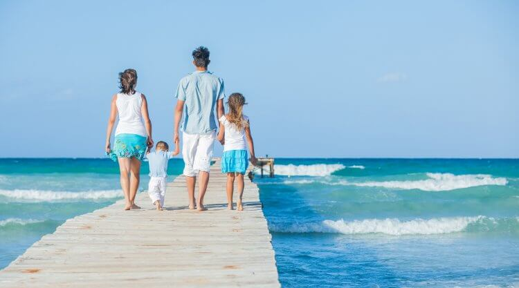 Family of four on wooden jetty by the ocean. Back view