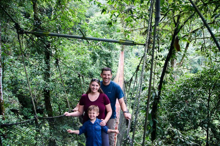 Family standing on a bridge in Rainmaker Park. Manuel Antonio, Costa Rica tours.