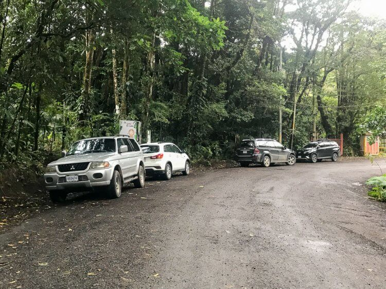 Cars parked alongside a dirt road at the entrance to the Monteverde Cloud Forest Reserve in Monteverde, Costa Rica