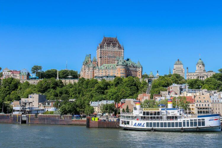 Large hotels in the background with the old city of Quebec below. The Lawrence river is in the foreground with a AML boat.