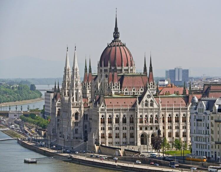 Parliament building in Budapest alongside the Danube river with cars on the streets and boats in the river.