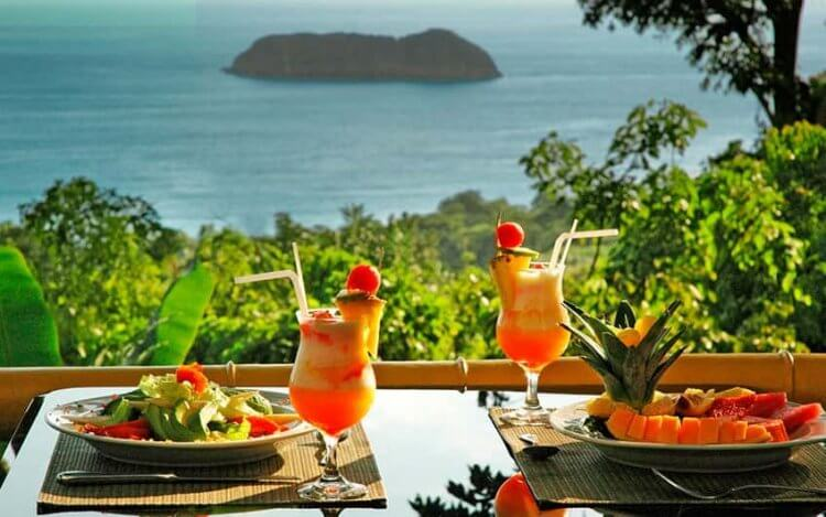 Recommended restaurants: two mixed drinks with lunch overlooking the ocean with an island in the background.