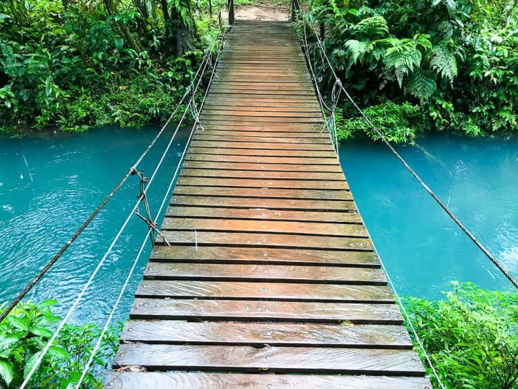 Costa Rica Rio Celeste one person bridge passing over the river.