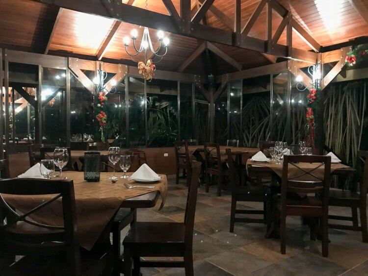 Evening view of the restaurant with wooden tables and chairs with white napkins and dim lights overhead.