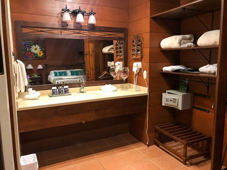 Photo of the bathroom area with double sink, shelving to the right with safe and luggage rack.