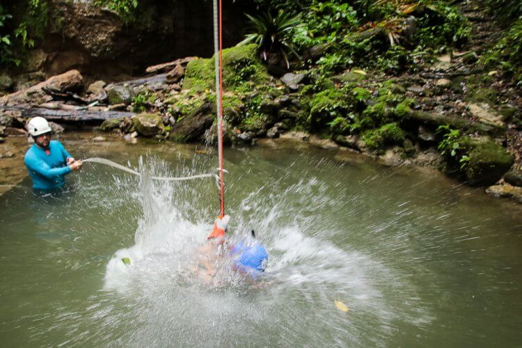 Man falling into a pool of water while hanging from a rope while waterfall rappelling in Arenal, Costa Rica.