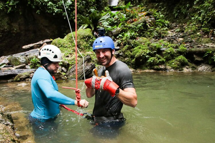 Man with a blue helmet and green shirt giving a thumbs up after dropping into a pool of water while waterfall rappelling in Costa RIca.