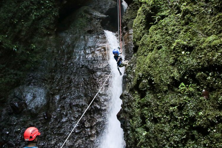 Little boy waterfall rappelling down the side of the canyon in Costa Rica.