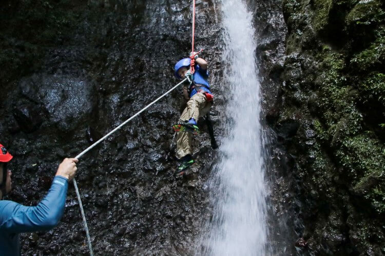 Little boy waterfall rappelling down the side of the canyon in Costa Rica. Pure Trek Canyoning Costa Rica.