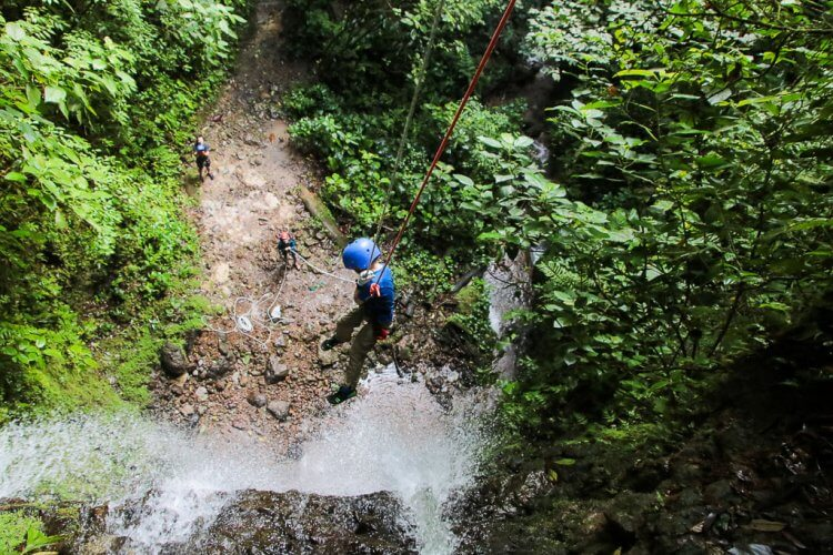 Little boy with a blue helmet and blue shirt rappelling over the side of a waterfall in Costa Rica.