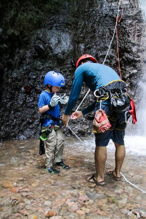 Guide with a blue shirt and red helmet helping a five year old boy with blue shirt and blue helmet to unclip the rope from his harness after waterfall rappelling.