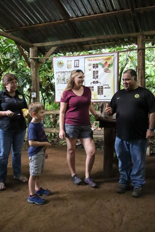 Woman, little boy and another woman standing next to a guide listening to him explaining the cocoa process.