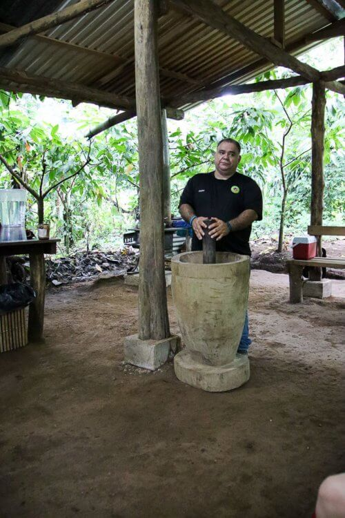 The guide standing over a pestle and motor getting ready to crush the cocoa seeds.