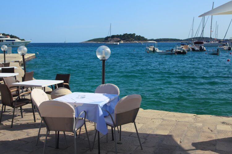 Tables of cafe on the embankment of the city of Hvar.