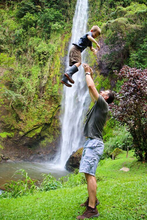 Father throwing his son into the air with the rainbow waterfall in the background.