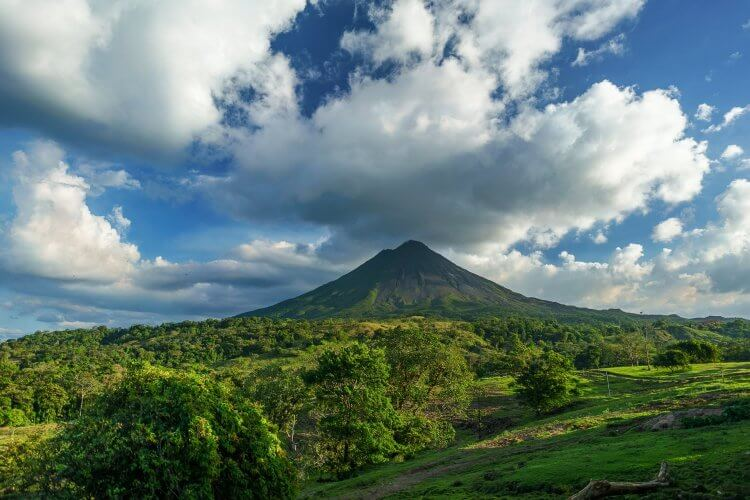 Arenal Volcano in the distance with a beautiful blue sky and white clouds. Visitors have so many choices of things to do in arenal costa rica.