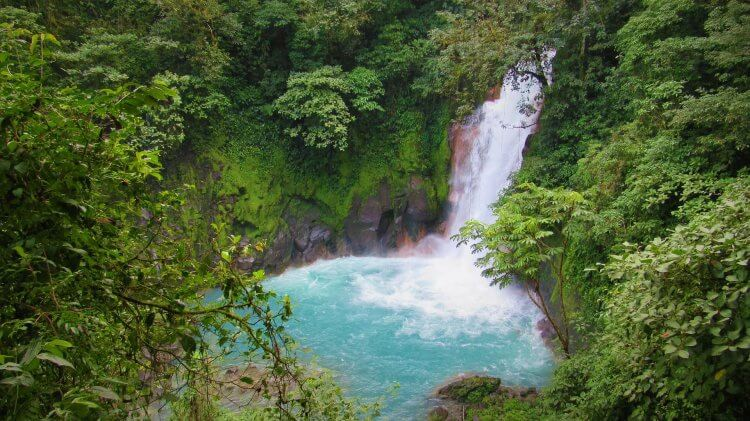 Rio Celeste waterfall with stunning blue water surrounded by the forest. It is one of the top rated places to visit near Arenal, Costa Rica.