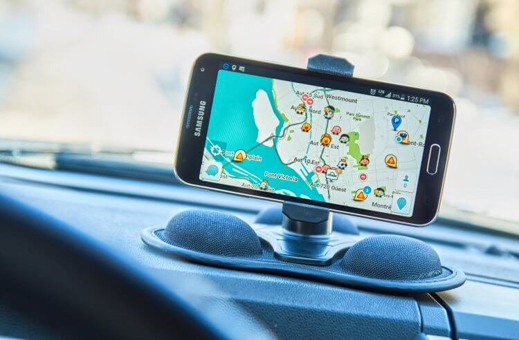 Phone on the dash of a vehicle with the GPS app Waze running.