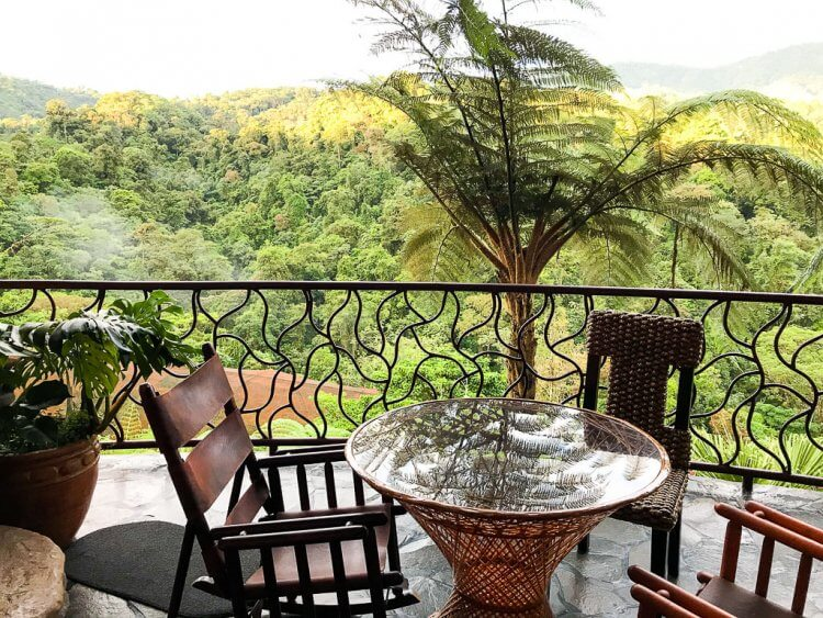 Patio with three chairs, a table and view over the valley at the Peace Lodge in Costa Rica.