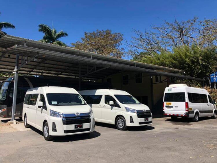Shuttle vans parked under a covering.