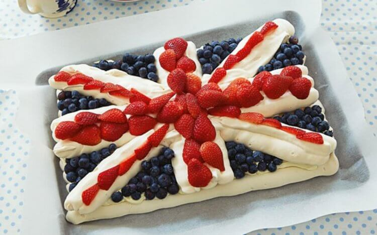 Cake with whip cream and berries shaped like the Great Britain flag.