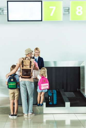 A family with a mother, father and two children standing at check-in at the airport with the baggage carousel to their right.