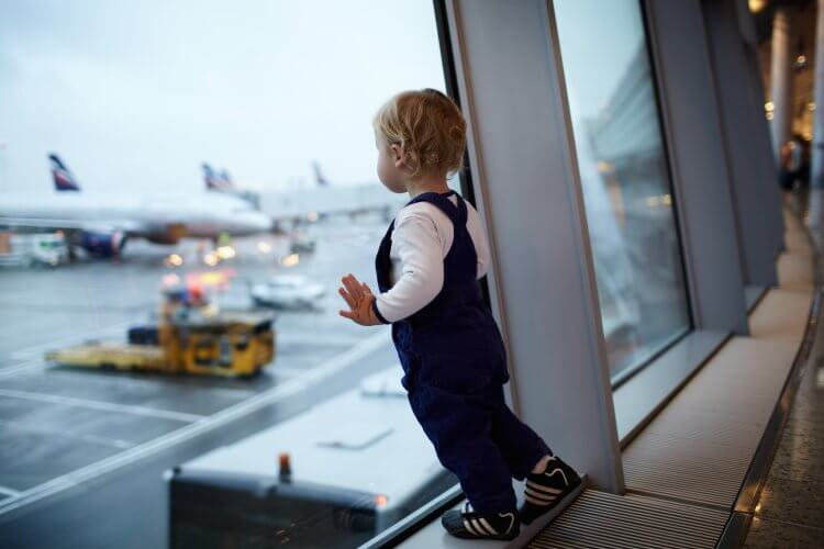 A toddler leaning against the window in an airport looking at the planes on the tarmac. The toddler is wearing overalls and a white shirt with curly blonde hair.